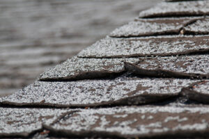 worn old shingles on a roof show signs needing a roof replacement
